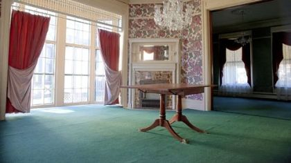 The dining room features large windows (there are 43 in the home), period wallpaper and the original fireplace mantel.