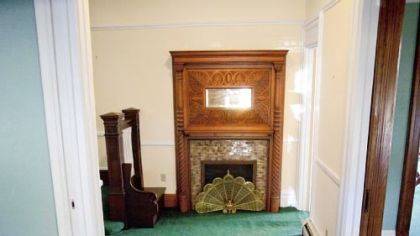 The front hall features a fireplace with mirror.