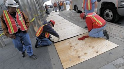 Metropolitan Transportation Authority workers cover subway ventilation grates with plywood Friday to help prevent flooding at South Ferry in New York.