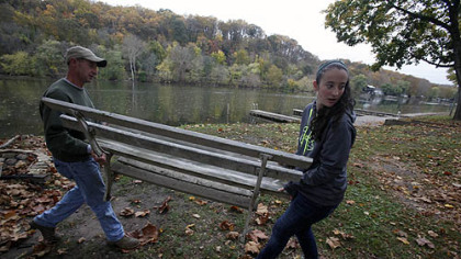 Jonathan Nice, left, and his daughter Emily, of Landsdale, Pa., move a bench to a shed as they help a friend pack up his private dock in preparation for severe weather.