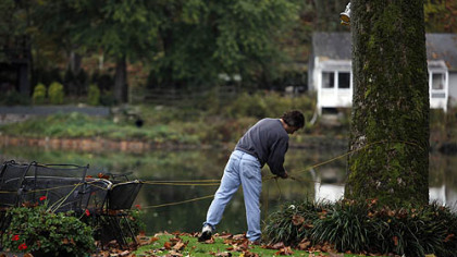 A man secures outdoor furniture to a tree on River Road along the Schuylkill River in Philadelphia.