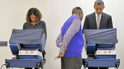 An election worker helps President Barack Obama as he completes early voting on Thursday at the Martin Luther King Community Center in Chicago.