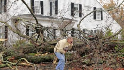 John Constantine makes his way out of his house after winds from Hurricane Sandy caused a tree to topple over and fall onto it Monday in Andover, Mass.