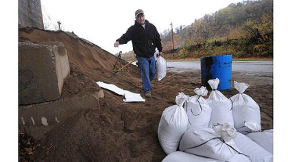 "Bob Hillard, who owns a plumbing shop in Millvale, fills sandbags at Riverfront Park in preparation for possible flooding from Hurricane Sandy. He suffered more than $100,000 in damage to his business from Ivan in 2004 and said he's ""paranoid and stressed."""