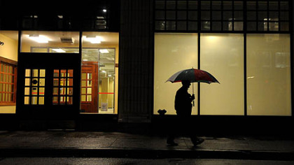 A pedestrian with an umbrella along Smithfield Street early Monday morning in a bit of a calm before the storm.