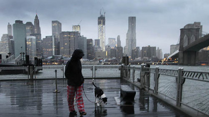 Vanessa Pumo walks her dog Bella as wind and rain from Hurricane Sandy arrive, Monday, Oct. 29, 2012 in Brooklyn, N.Y. Behind her is the Manhattan skyline and Brooklyn Bridge, right.