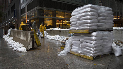 A working crew stacks sandbags beside concrete barriers to protect buildings near the World Financial Center in anticipation of massive flooding, Monday, Oct. 29, 2012, in New York.