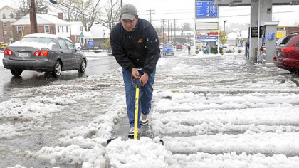 Angel Rodriguez, 22, removes snow at a gas station parking lot on Tuesday in Morgantown, W.Va.