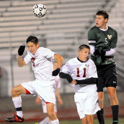 Pine-Richland&#039;s Patrick Sullivan heads a ball at midfield against Upper Saint Clair&#039;s Ethan Dysert, left, and Adam Heil.