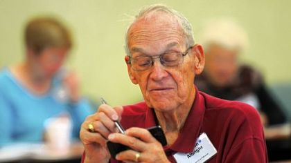 Denton Albright from Penn Hills works with a stylus to type on a smartphone at the Senior TechRally at Longwood at Oakmont.
