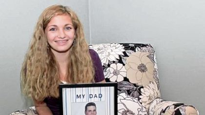 Logan Robinson, 13, holds a photo of her father, R.J., who died from pancreatic cancer. She will pour purple dye into the fountain at Levin Furniture in Monroeville at 12:30 p.m. today to raise awareness of the disease.