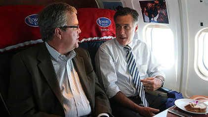 Republican presidential candidate Mitt Romney talks with former Florida Gov. Jeb Bush aboard his campaign plane on Wednesday en route to Miami.
