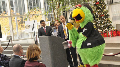 The Pirate Parrot stands by with Steely McBeam as Andy Wisniewski, vice president of Highwoods Properties./PPG Place, center, talks about the ice rink and the planned mascot skate during a press conference today.