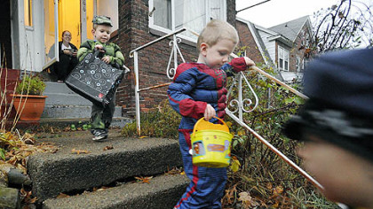 Supertwins Liam Harencame, left, as the Hulk, and Garret Harencame, center, as Spiderman, trick-or-treat at the home of Cortney Meade, background, in Lawrence Park, Pa., on Wednesday. Ms. Meade said despite the rain, she enjoyed handing out candy.