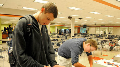 Upper St. Clair seniors Josh Simmons and Alex Bloom mark their ballots today at the school's cafeteria.