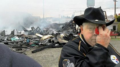 Valley Billiards owner Burley Hartin dabs his eyes while his business near New Alexandria smolders in the background on Friday.