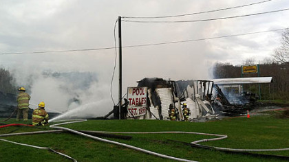 Water is poured on the fire at Valley Billiards along Route 119.