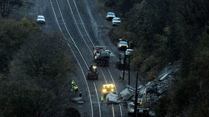 Crews work around sunrise to clear boulders on the Norfolk Southern railroad tracks above West Carson Street. The first train was able to pass the site by 7:24 a.m.