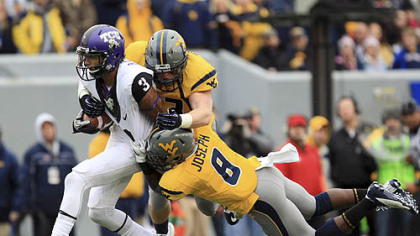 West Virginia's Jared Barber (33) and Karl Joseph (8) tackle TCU's Brandon Carter during the first half.