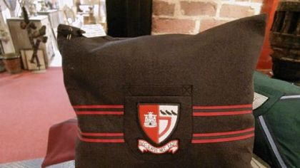 Private school blazer crests on pillows from Fanshawe Blaine Antiques & Interiors.
