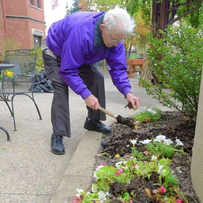 Joseph Grindel pulls out annuals at Canterbury Place.