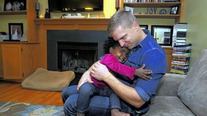 Rob Szenyeri hugs his daughter, Mae, in the family room of their Cranberry home.