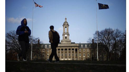 Students walk in front of the Old Main building on the Penn State campus in State College, Pa.