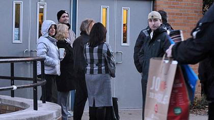 Voter wait outside at 6:45 a.m. at the entry to the poll in the city's Minadeo Elementary School.
