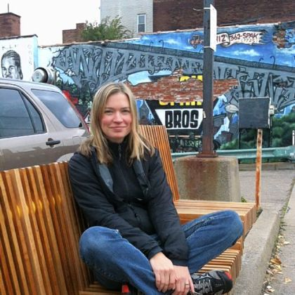 Landscape architect Rebecca Mizikar on the bench she designed at Penn Avenue and Winebiddle Street.