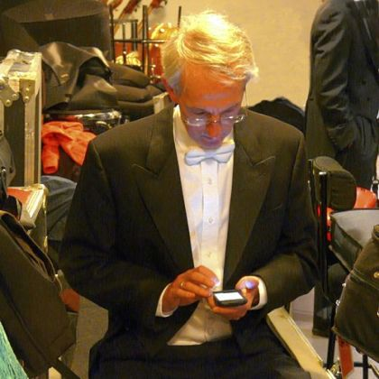 PSO cellist Hampton Mallory checks his email amid backstage chaos in Paris.