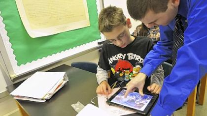 Eighth-grader Ben Deily, 13, works with his teacher Joe Welch, who helped develop a social studies book for North Hills Junior High Students using iBook Author, an app for tablets.