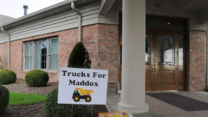 A dump truck is left at the entrance of the Slater Funeral Home in Scott on Thursday in honor of Maddox Derkosh.