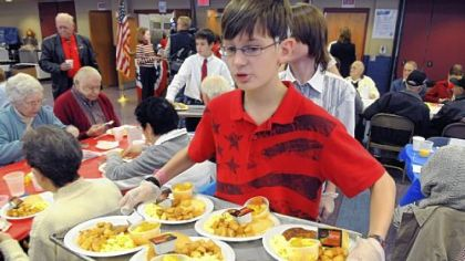 Andrew Lesnett, a seventh-grader at Shaler Area Middle School, carries a tray of food for awaiting veterans during the school district's Celebration of Veterans breakfast Wednesday at the middle school.