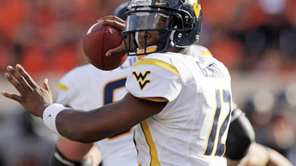 West Virginia quarterback Geno Smith looks for an open receiver during the first half.