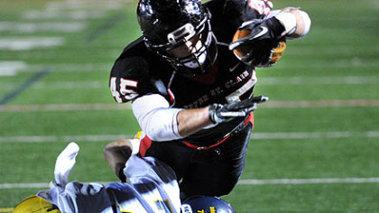 Upper St. Clair running back Mac Pope dives over Central Catholic's Todd Coles for a 5-yard touchdown in the first half Friday at Baldwin High School.