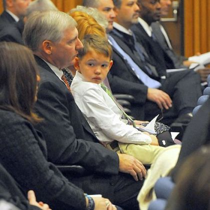Joey O'Donnell, 8, sits on his father's lap during the Law Enforcement Agency Directors awards ceremony at the University of Pittsburgh's Barco Law Building on Friday. Kevin O'Donnell, Joey's father, is a special agent with the Internal Revenue Service in the Criminal Investigation Division.