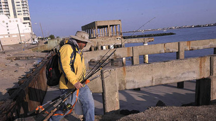 Ray Guangon of Cherry Hill, N.J., crosses over the remains of the boardwalk north of the casino district in Atlantic City to go fishing today. The boardwalk in front of the casinos remained intact, only an older section of the boardwalk north of the Revel casino was demolished.