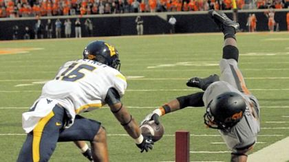 Oklahoma State receiver Josh Stewart, right, dives in for one of his three touchdowns Saturday against West Virginia. Stewart caught 13 passes for 172 yards and also rushed for 46.