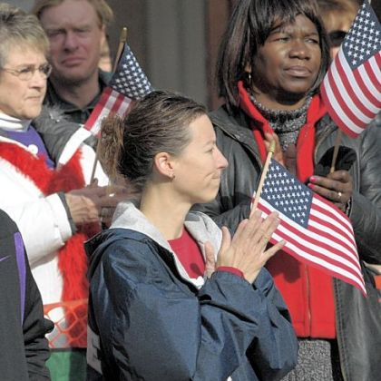 Spectators listen to the national anthem during Saturday's Veterans Day Parade, Downtown. One of the largest Veterans Day parades in the nation, this year's was dedicated to post-9/11 war veterans and their families.