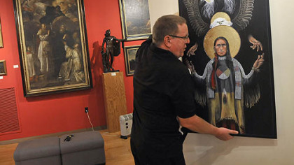 Brother Nathan Cochran hangs art for the upcoming Nationwide Juried Catholic Arts Exhibition.
