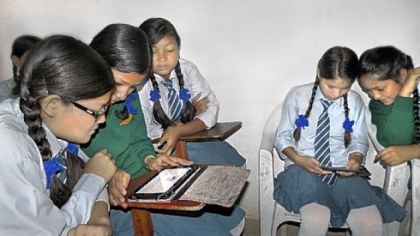 Girls sponsored by the Rukmini Foundation explore e-readers donated for their use.