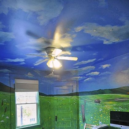 A mural with blue skies and fluffy clouds fill the 14- by 12-foot ceiling in one of the bedrooms.