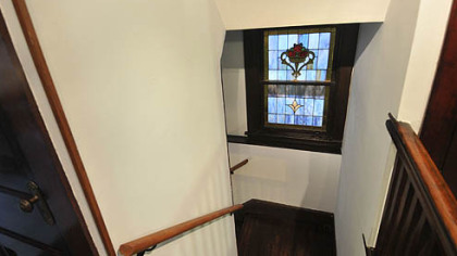 Stained glass window on staircase landing between first and second floor.