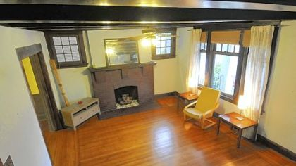 The living room features a brick fireplace and  horizontal wood beams across the ceiling.