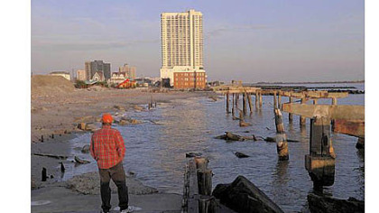 Randy Rocha of Cherry Hill, N.J., surveys a section of boardwalk destroyed by Superstorm Sandy in northern Atlantic City. The boardwalk in front of the resort city?s casinos remains intact.