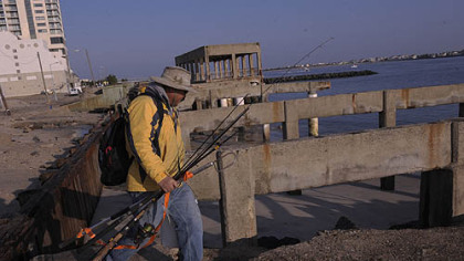 Ray Guangon, of Cherry Hill, N.J., crosses over the remains of the boardwalk north of the casino district in Atlantic City to go fishing on Saturday. The boardwalk in front of the casinos remained intact. Only an older section of the boardwalk north of the Revel casino was demolished.