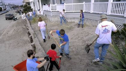 Relatives of the Hoover family help shovel feet of sand Saturday from around the exterior of the family beach home in Ocean City, N.J. From left, Andrew Malloy of Carlisle, Pa., Alex Elicker, 3, with his brother Ethan Elicker, 10, both of Elizabethtown, Pa., and Ken Hoover of Lancaster, Pa.