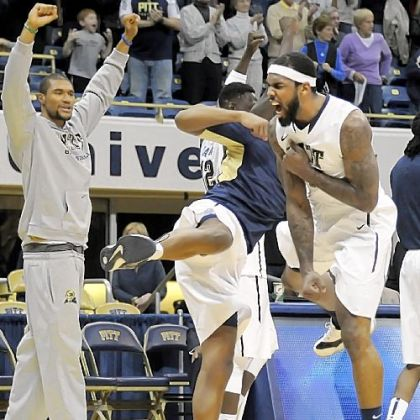 Pitt's J.J. Moore, right, celebrates the Panthers' 72-62 comeback win against Oakland in overtime Saturday at Petersen Events Center.