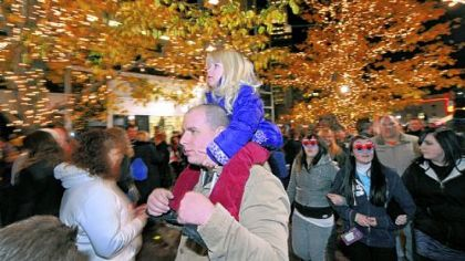 Haily Pollack, 3, of Port Vue sits atop her father Brad's shoulders as he makes his way through the crowd at PPG Place Plaza during Light Up Night festivities on Friday.