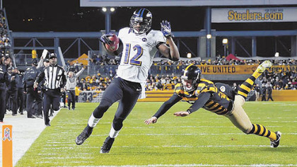 The Ravens&#039; Jacoby Jones runs into the end zone on a punt return as the Steelers&#039; Drew Butler tries to make the tackle in the first quarter at Heinz Field.